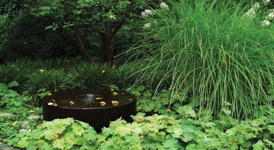 Schröer zeigt Mühlstein im Garten.