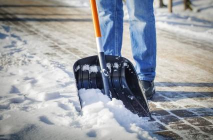 Schröer Garten- und Landschaftsbau zeigt eine Person mit Schaufel beim Schneeräumen
