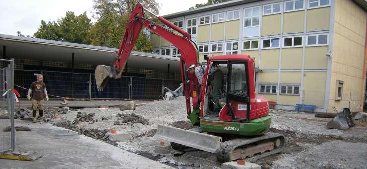 Schröer Garten- und Landschaftsbau Bagger auf ausgehobenem Untergrund vor Schule