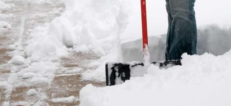 Schröer Garten- und Landschaftsbau Person schaufelt Schnee als Winterservice
